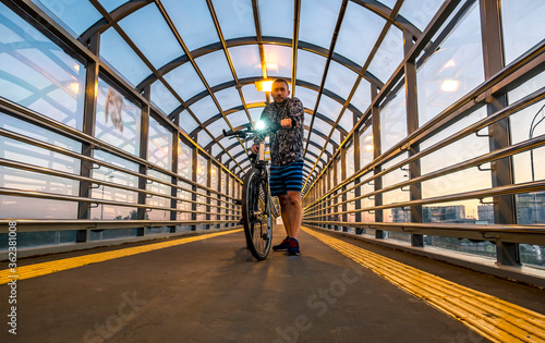 A man with a Bicycle in an overpass over the Pulkovo highway in Saint Petersburg #362381008