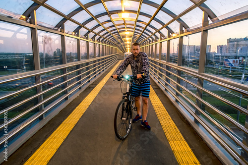 A man with a Bicycle in an overpass over the Pulkovo highway in Saint Petersburg #362381052
