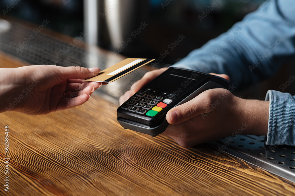 Fototapeta Modern contactless payment of bill in pub. Client hand holds credit card, bartender holding terminal