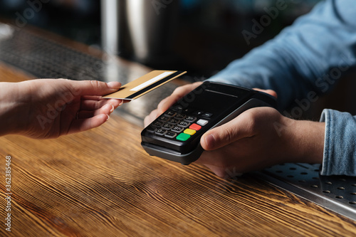 Fototapeta Modern contactless payment of bill in pub. Client hand holds credit card, bartender holding terminal obraz