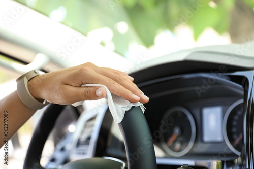 Fotografiet Woman cleaning steering wheel with wet wipe in car, closeup