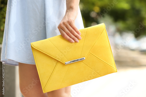 Fotografiet Young woman with elegant envelope bag outdoors on summer day, closeup