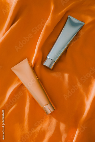 Shiny light blue and golden cosmetic tubes on sunny orange fabric background Poster Mural XXL