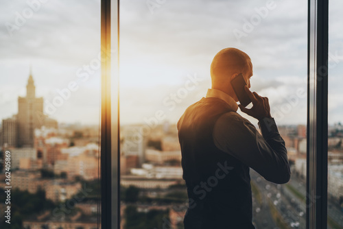 Fototapeta Silhouette of caucasian man entrepreneur having a phone conversation while stand