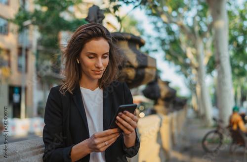 Fotografia focus on businesswoman in suit calling on cell phone in park, portrait elegant w