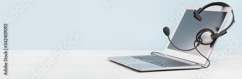Obraz na plátně Laptop with blank screen with headphones on desk blue background