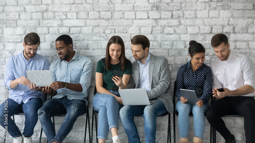 Six multi racial millennial girls and guys sit in line on chairs against grey wa Canvas