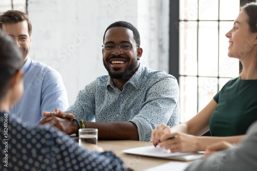 Fototapeta Multi-ethnic company staff gathered together at briefing meeting, focus on African team leader enjoy communication with workmates listening associates working on project, take break having fun concept obraz