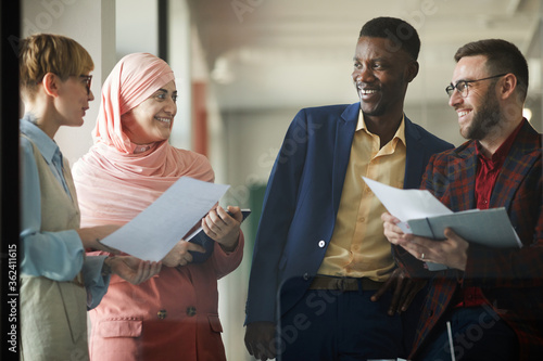 Waist up portrait of successful multi-ethnic business team talking to each other and smiling while standing in office interior