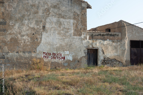 Fotomural protest slogan on a wall of an abandoned village