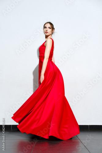 Carta da parati Portrait of girl in waiving red silk dress