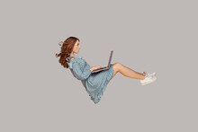 Hovering In Air. Surprised Girl Ruffle Dress Levitating, Looking At Laptop Screen Shocked Amazed, Surfing Web Social Networks While Flying In Mid-air. Indoor Studio Shot Isolated On Gray Background