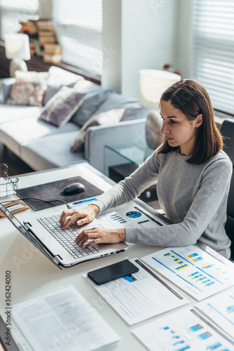 Focused woman working from home office on laptop - fototapety na wymiar