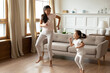 Energetic young vietnamese ethnic mother enjoying playtime with funny crazy asian child daughter, dancing to favorite disco music barefoot in modern living room, hobby weekend pastime indoors.