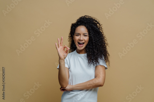 Half length shot of joyful curly young woman makes okay gesture, enjoys life and says ok, confirms everything is fine, wears white t shirt, isolated on beige background Fototapet