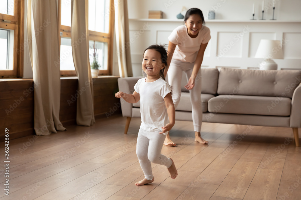 Fototapeta Full length overjoyed little preschool cute vietnamese ethnic baby girl running barefoot on warm floor, having fun playing with energetic young asian mother or nanny, leisure daycare activity.