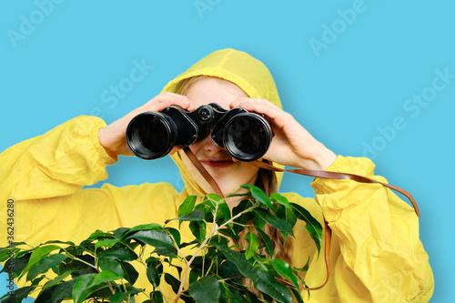 Fotografie, Tablou A Caucasian little girl in a yellow jacket looks through large binoculars