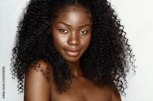 Fashion portrait of young beautiful african american woman with curly hair againstgray background