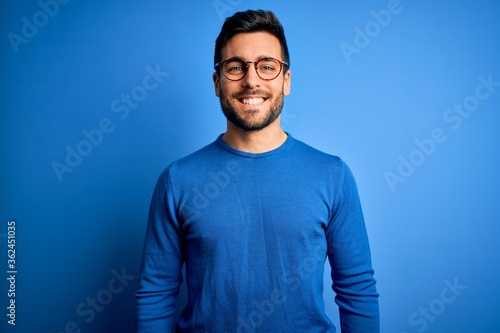 Young handsome man with beard wearing casual sweater and glasses over blue background with a happy and cool smile on face. Lucky person.