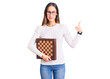 Beautiful brunette young woman holding chess smiling happy and positive, thumb up doing excellent and approval sign
