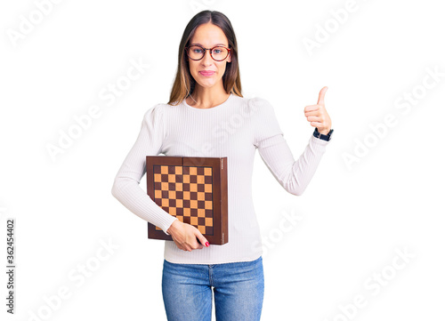 Obraz Beautiful brunette young woman holding chess smiling happy and positive, thumb up doing excellent and approval sign - fototapety do salonu