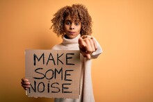 African American Activist Woman Asking For Revolution Holding Banner With Make Noise Message Pointing With Finger To The Camera And To You, Hand Sign, Positive And Confident Gesture From The Front