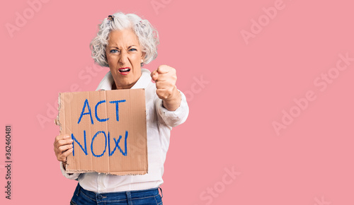 Fototapeta Senior grey-haired woman holding act now banner annoyed and frustrated shouting with anger, yelling crazy with anger and hand raised obraz