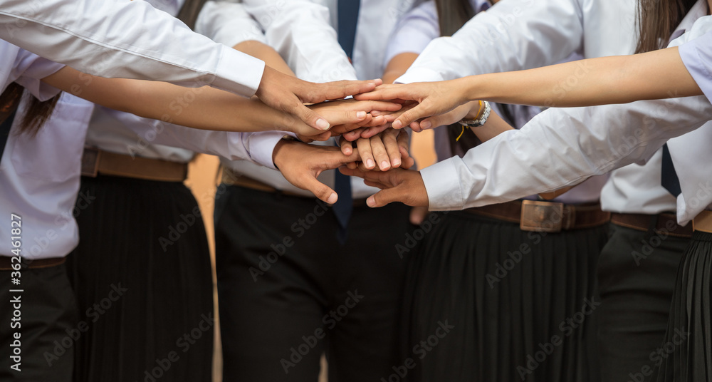 Fototapeta A group of men wearing white shirts standing in shaking hands outdoor ,concept teamwork.