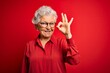 canvas print picture - Senior beautiful grey-haired woman wearing casual shirt and glasses over red background smiling positive doing ok sign with hand and fingers. Successful expression.