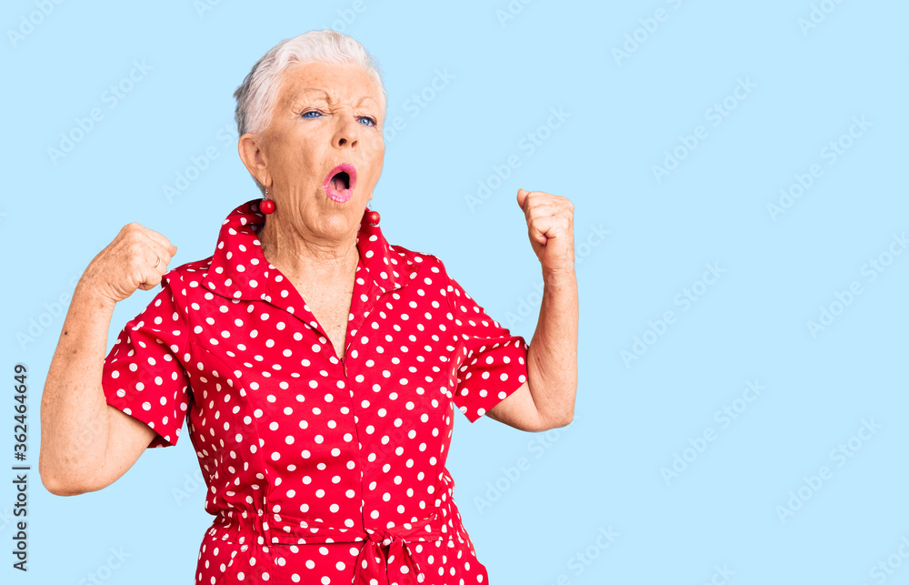Fototapeta Senior beautiful woman with blue eyes and grey hair wearing a red summer dress showing arms muscles smiling proud. fitness concept.