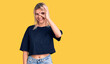 Leinwanddruck Bild - Young beautiful blonde woman wearing casual t-shirt doing ok gesture with hand smiling, eye looking through fingers with happy face.