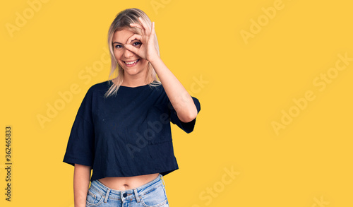 Young beautiful blonde woman wearing casual t-shirt doing ok gesture with hand smiling, eye looking through fingers with happy face. - 362465833