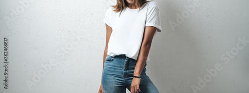 Fototapeta Pretty caucasian woman in white blank t-shirt, grunge wall, studio portrait. Wide screen, panoramic obraz