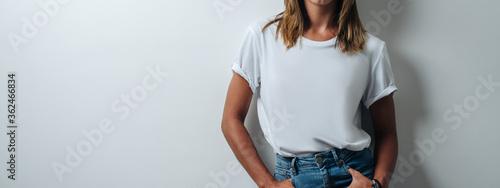 Fotografie, Obraz Playful woman in white blank t-shirt wearing glasses, empty wall, horizontal studio portrait