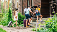 It Will Be Our Hotel. A Photo Of A Family With Suitcases And Backpacs On A Summer Weekend Coming To The Wooden Hotel Surrounded By Trees, Father Holding His Daughter's Hand.