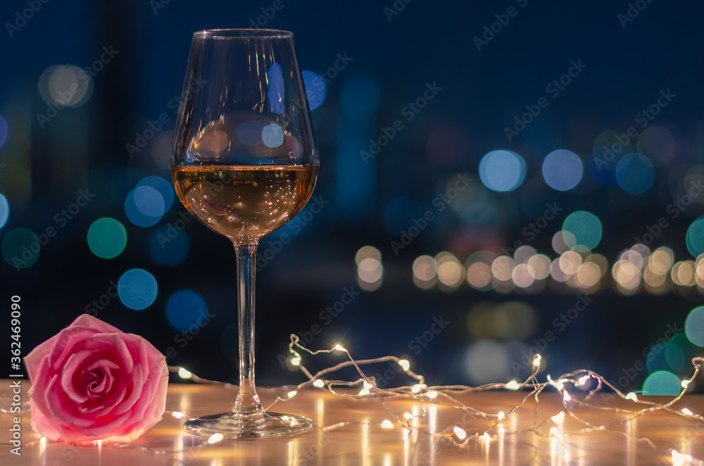 Fototapeta A glass of Rose wine with rose flower on table and colorful city bokeh light background.