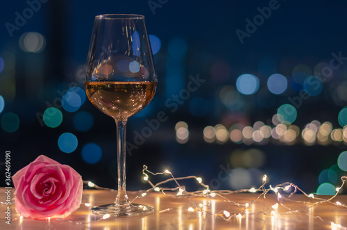 Obraz A glass of Rose wine with rose flower on table and colorful city bokeh light background. - fototapety do salonu