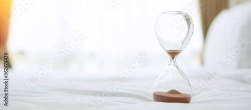 Hourglass on bed in the morning sunlight, Sand flowing through the bulb of Sandglass measuring the passing time Fototapet