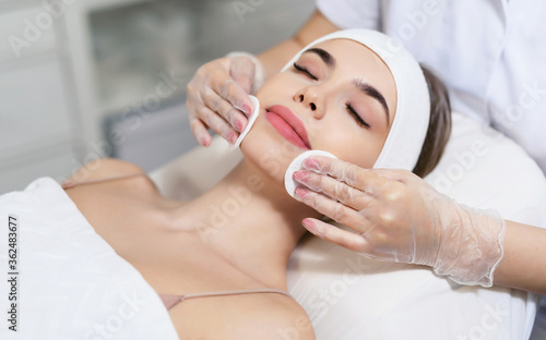 Fotomural Close up of beautician hands doing facial cleansing of a young woman using cotton pads or sponge in a beauty clinic or spa