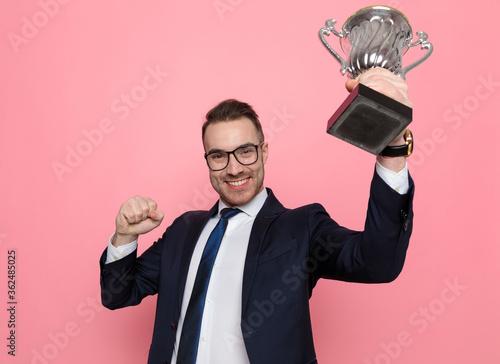 Obraz na plátně proud elegant businessman holding up trophy and celebrating