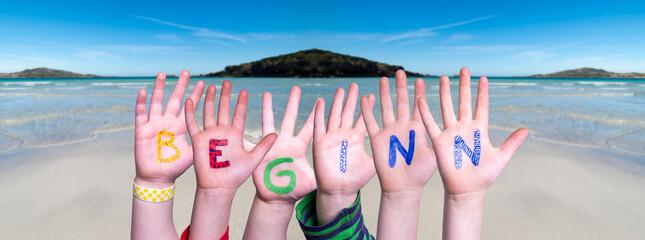 Children Hands Building Colorful German Word Beginn Mean Beginning. Ocean And Beach As Background