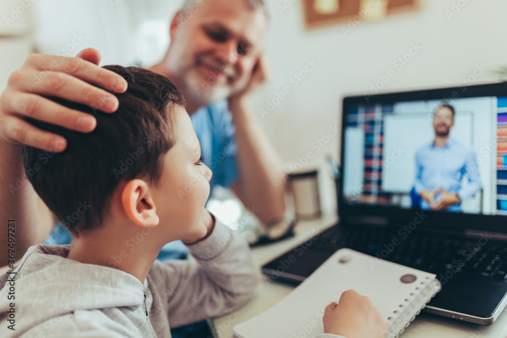 Fototapeta Schoolboy educate online. Father helps his son with home work. Boy in video conference with teacher on laptop at home.
