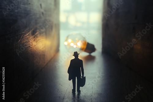 Fotomural Surreal image of person in dark corridor looking at glowing light bulb