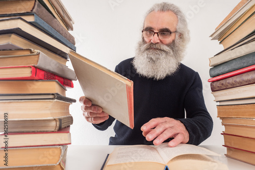 An elderly man among the books Wallpaper Mural