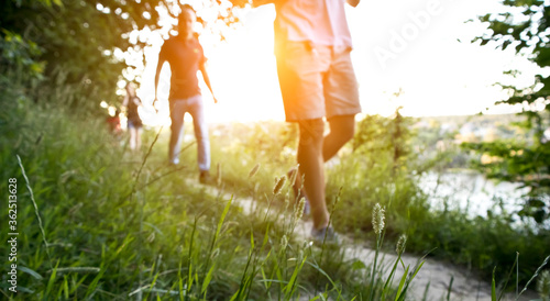 Fotomural Blurred view of  friends are walking through the pathway on the hill