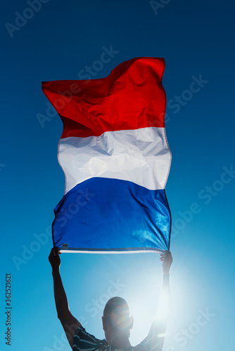Fototapeta man waving a french flag on the wind obraz