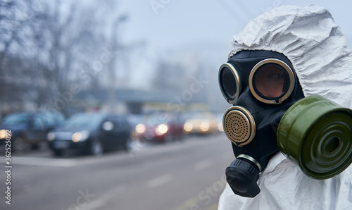 Fototapeta Close up of ecologist in safety respirator looking at camera while standing on the street