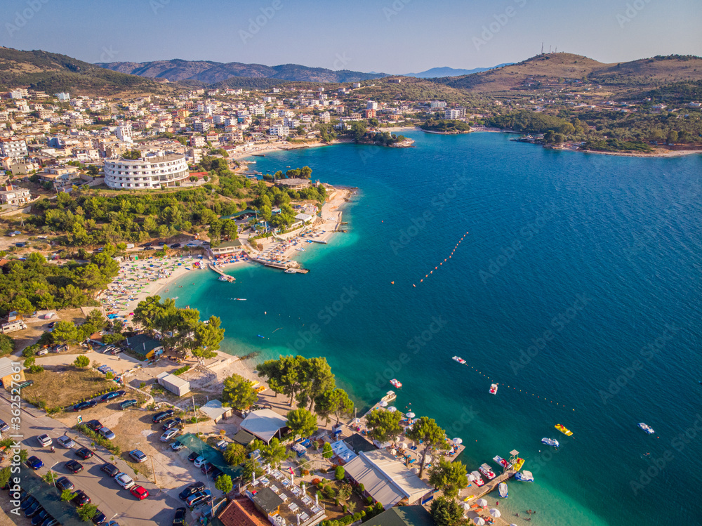 Fototapeta Aerial view of the coastline of the resort town of Ksamil on a sunny summer day. Albania.