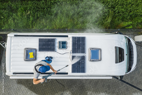 Men Pressure Washing RV Camper Van Roof Equipped with Solar Panels Fototapeta