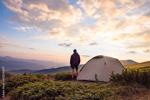 tourist tent and sportsman in mountains, summertime Canvas Print